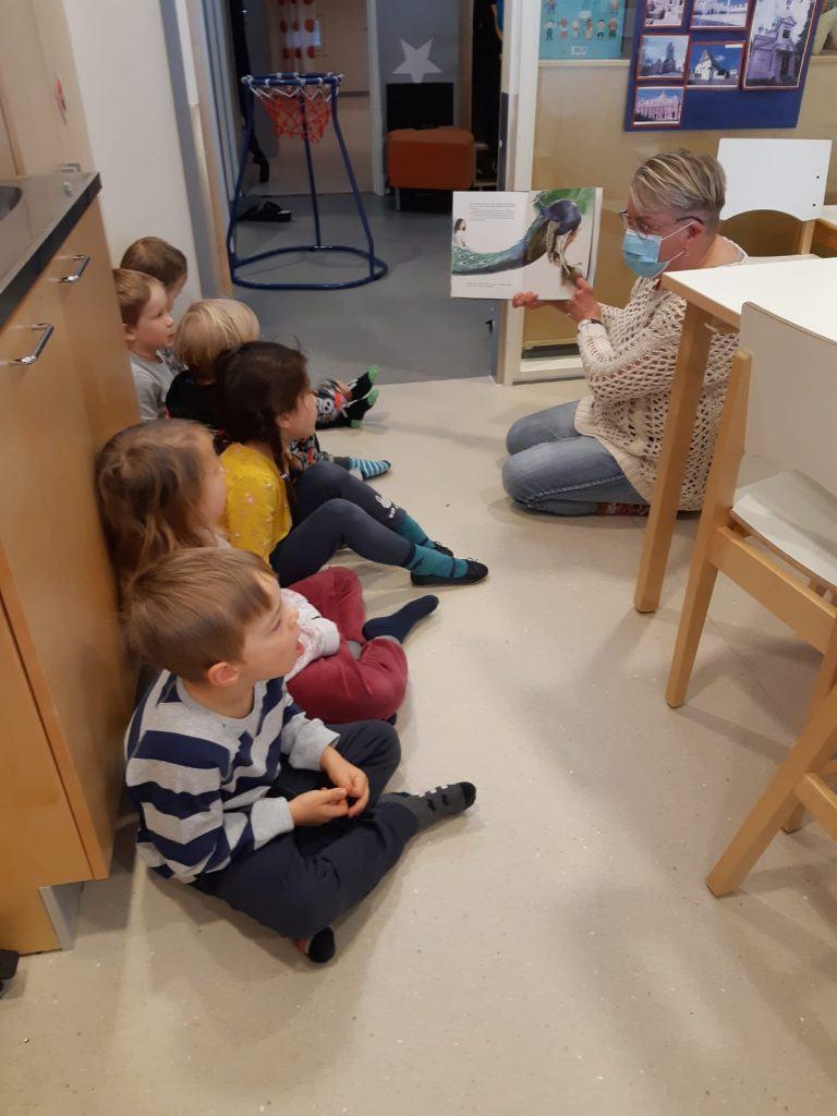 Päiväkodin lapset istuvat rivissä seinään nojaten. Päiväkodin työntekijä näyttää lapsille kuvaa.
