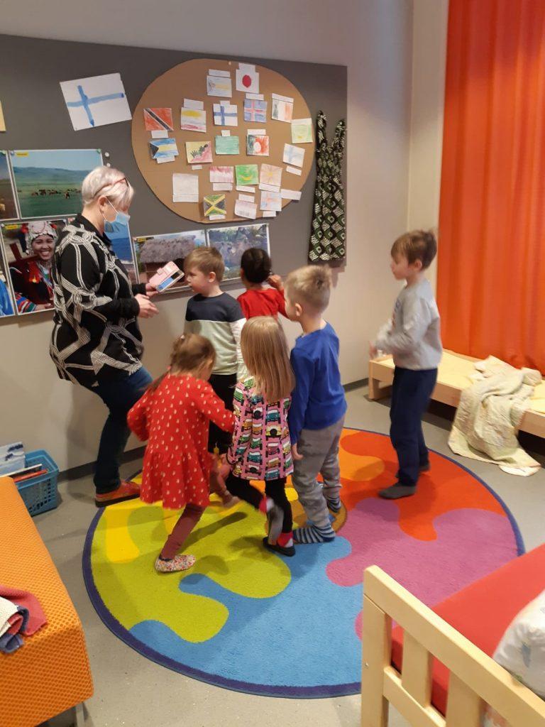 Päiväkodin lapset kuuntelevat päiväkodin työntekijän lukemista ja leikkivät värikkäällä matolla. Osa katsoo seinälle askarreltua työtä.