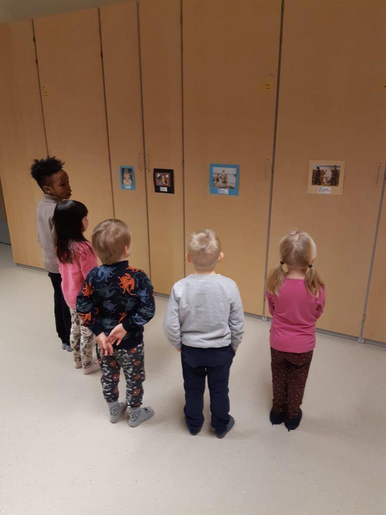 Kuvassa viisi päiväkodin lasta katsoo rivissä seinälle kiinnitettyjä pahvisia kuvia.